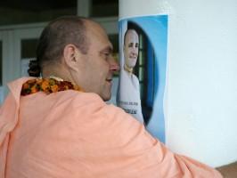 Джаяпатака Свами обнимает колону с плакатом, на котором изображен Джаянанда, со словами: «Мой любимый вартма-прадаршака-гуру»