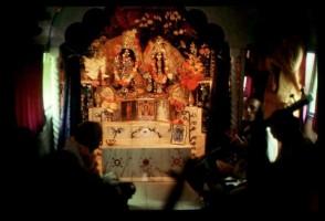 """Шрила Прабхупада (слева) в автобусе группы """"Радха-Дамодара"""". По центру на алтаре Божества Радхи-Дамодары, справа Вишнуджана Свами и Дхриштадьюмна дас. Чикаго, 1975 г."""